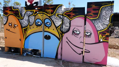 Bright faces on old Fridges at a recycling festival.