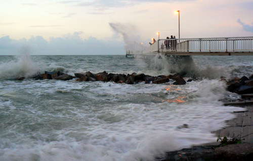 Waves wash over the boat ramp breakwater at high tide